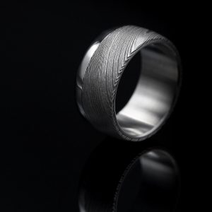 Curved shape damascus ring with steel stripe. | Kaareva Damacussormus teräsraidalla. | Design Kultaseppä Goldsmith Petri Pulliainen.
